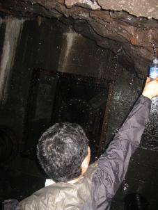 Taro Uchida sampling the water from the Waihe'e Tunnel.